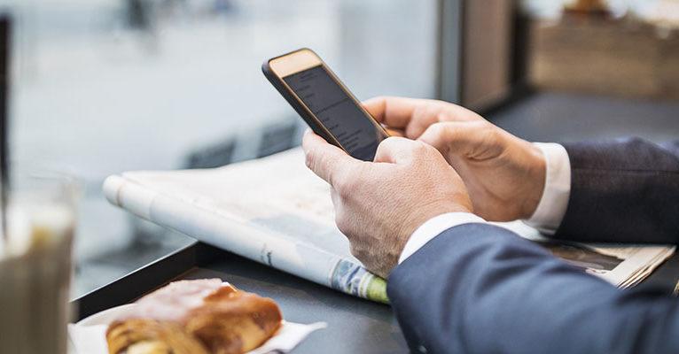 Mann hält Smartphone in Cafe